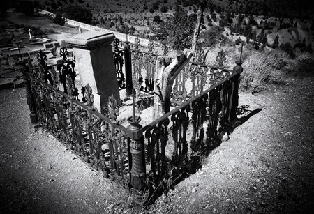 Grave in an old cemetery that has been left to the elements done in a black and white Film Noir grainy effect for Halloween Stock Photo