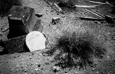Scary cemetery showing an old grave in which the grave marker has been torn off done in a Black and White Film Noir grainy effect for Halloween.
