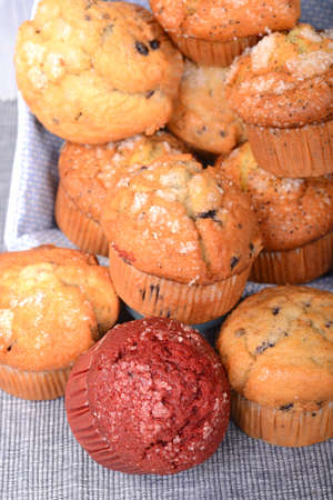 Variety of delicious muffins spilling out of a basket