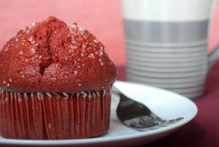 Warm delicious red velvet muffin served on a plate with a cup of coffee Stock Photo