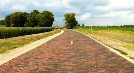 Original section of Route 66 which is 1.4 miles of hand-lain brick road and was completed in 1931. The road curves through the corn fields near Auburn, Illinois. Stock Photo