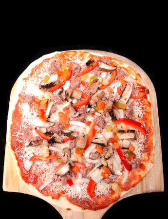Freshly made pizza with onions, peppers, sausage, cheese and tomato sauce on a peal waithing to be baked