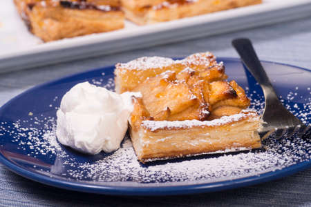Piece of an apple tart baked in puff pastry with an apricot glaze dusted in powdered sugar and served with fresh whipped cream.