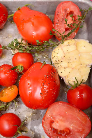 Freshly roasted tomatoes, garlic, onions, and herbs in preparation for a delicious tomato soup Stock Photo
