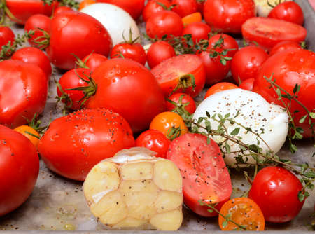 Fresh tomatoes, garlic, onions and thyme in roasting pan ready for roasting to make delicious tomato and basil soup