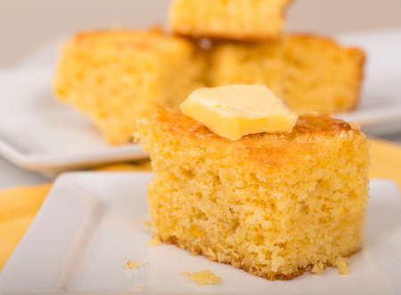 Piece of freshly baked cornbread with creamy butter on top.
