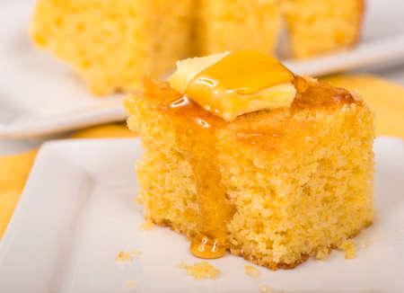 焼きたてのコーンブレッドにバターと蜂蜜が垂れ下がる 写真素材