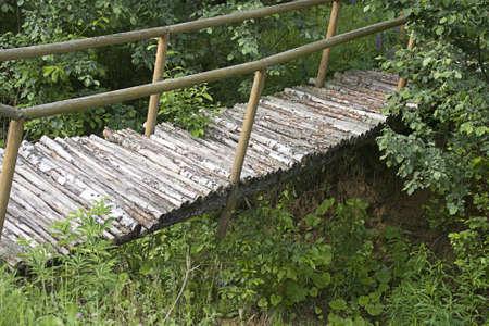 Wooden suspension bridge in forest photo