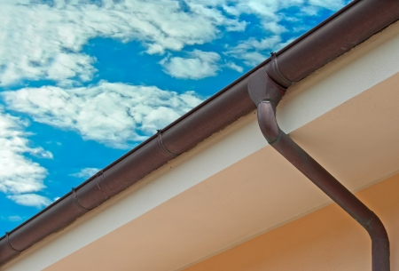 house roof: copper gutter under a cloudy sky