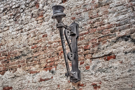 metal fastener: ancient wall candle holder in a brick wall
