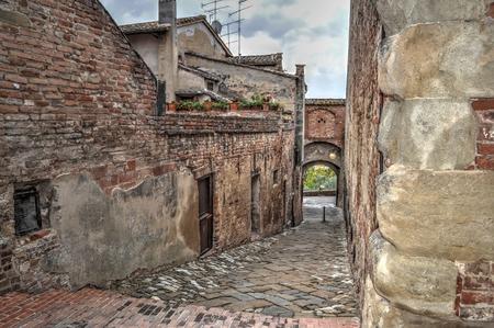 empedrado: edificios antiguos por una calle pavimentada en Certaldo