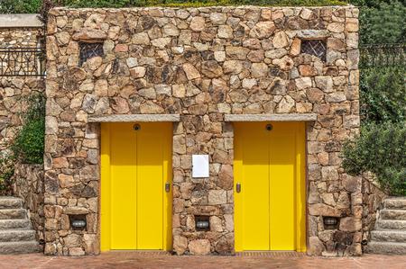 elevators: yellow elevators in a stone wall