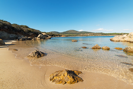 rocks and yellow sand in a hidden cove in Alghero, Sardinia Stock Photo