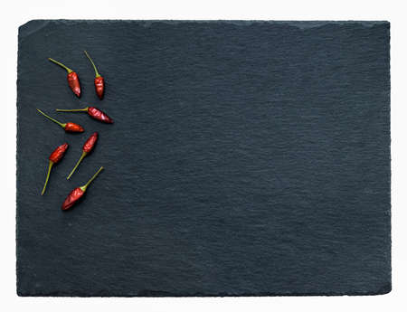 top view of small red peppers that lie on a black slate tray