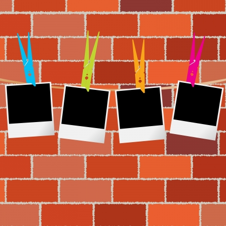 clothes pegs: Blank photo frames with clothes pegs on rope over brick wall