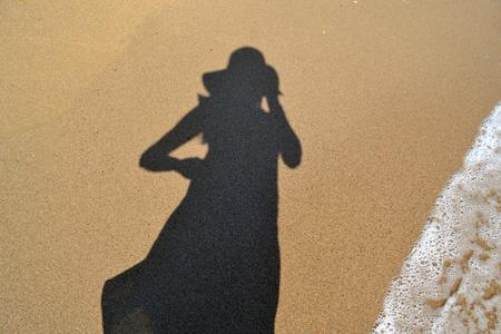 woman shadow: Woman shadow on the beach sand Stock Photo