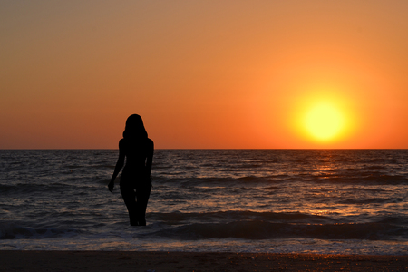 lady silhouette: Silhouette of a girl in the water at sunrise