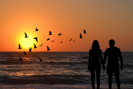 View of a full body of couple silhouettes holding hands looking at sunrise on the beach Stock Photo
