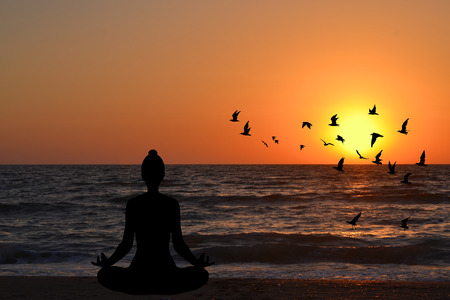 woman sunset: Woman meditating in a yoga pose on the beach at sunrise Stock Photo