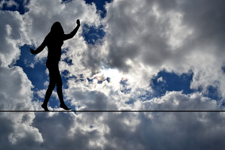 Woman silhouette balancing on rope over blue sky Banque d'images