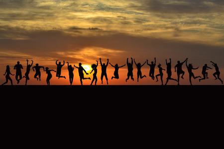Happy men and women silhouettes jumping at sunrise