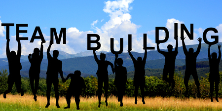 Silhouettes of people holding letters with TEAM BUILDING at mountains