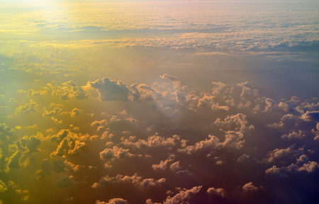 Sky, cloud formations and sun rays seen from the plane
