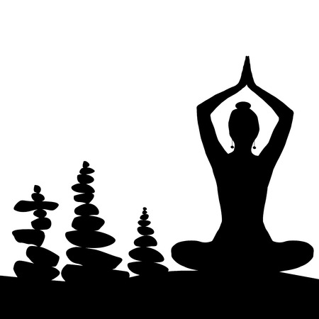 Silhouette of woman in yoga posture and balanced stones