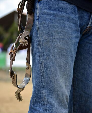 Western riding spurs hanging on belt