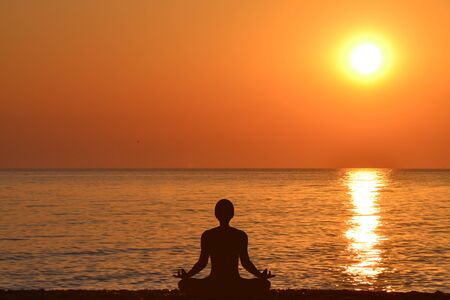 Yoga silhouette of a man sitting in lotus pose against the background of the sea and sunrise 写真素材