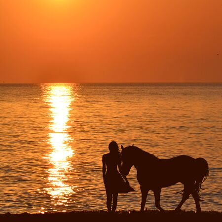 Woman with a horse at sunrise on the sea shore
