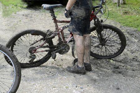 Mountain bike cyclist and dirty bike on a muddy road Stock Photo