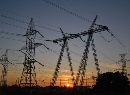 Electric Power Transmission with High Voltage Power Lines Supplies Electricity at sunset