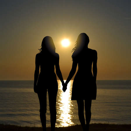 Back view of two women on holiday travel vacation beach watching sunrise