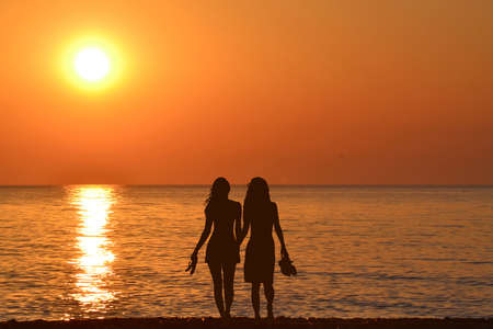 Two  young women holding hands walking barefoot with slippers in his hand on the beach