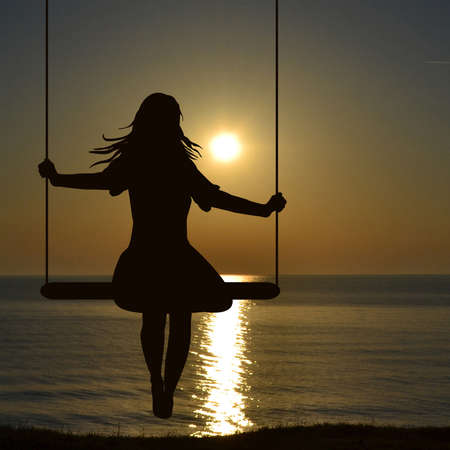 A young woman silhouette who is swinging at the sea shore whaching sunrise