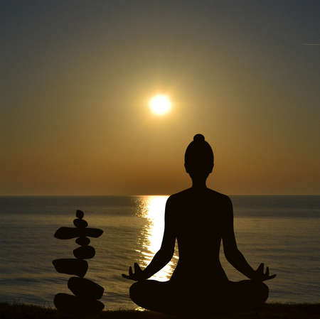 Silhouette of yogi in lotus position and a pile of stone at sea shore at sunrise