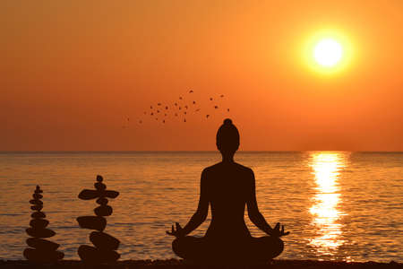 Silhouette of yogi in lotus position and a piles of stones at sea shore at sunrise