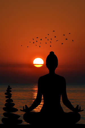 Silhouette of yogi in lotus position and a pile of stone at sea shore at sunset