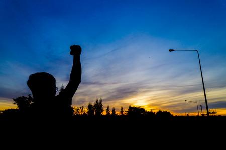 Men raise their hands in the sunrise