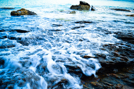 Waves breaking on the rocks photo