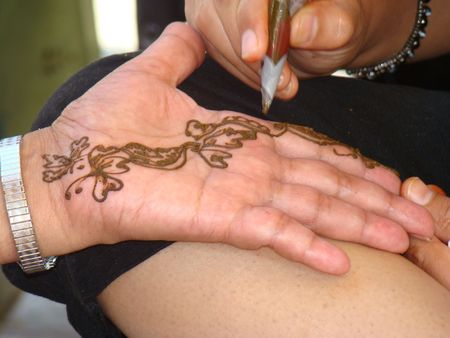 appling henna tattoo to hands