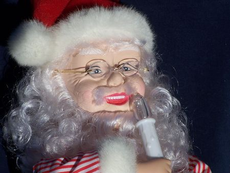 santa with a twinkle in his eye holding candle Stock Photo