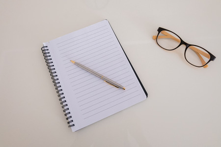 eye pad: A blank notebook with a pen and glasses
