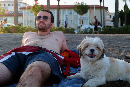 A man and a dog sitting on a beach in summer Stock Photo