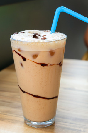 fredo: Iced coffee latte with chocolate sauce on wooden table Archivio Fotografico