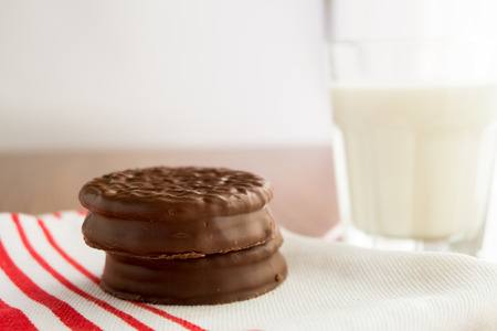 medium group of objects: Chocolate cookies on white linen napkin and a glass of milk on wooden, selective focus