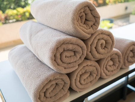 Pile of rolled up spa brown towel Stock Photo