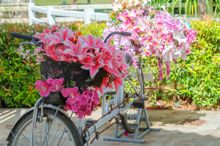 Bouquet of red flowers in a bicycle basket