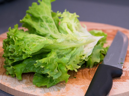 hand bell: cutting green leaf lettuce on a wooden board Stock Photo